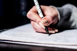 woman using a pen to write an essay in her notebook