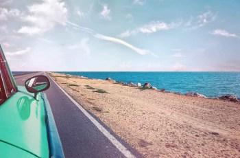 green car near seashore with blue ocean