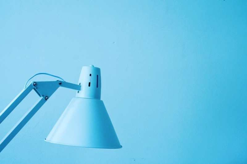 blue desk lamp against a blue wall