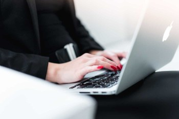 Business Woman With Red Finger Nails Typing on a Macbook Pro