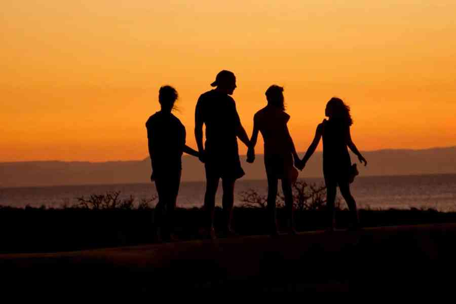 Family standing together while looking at the sunset
