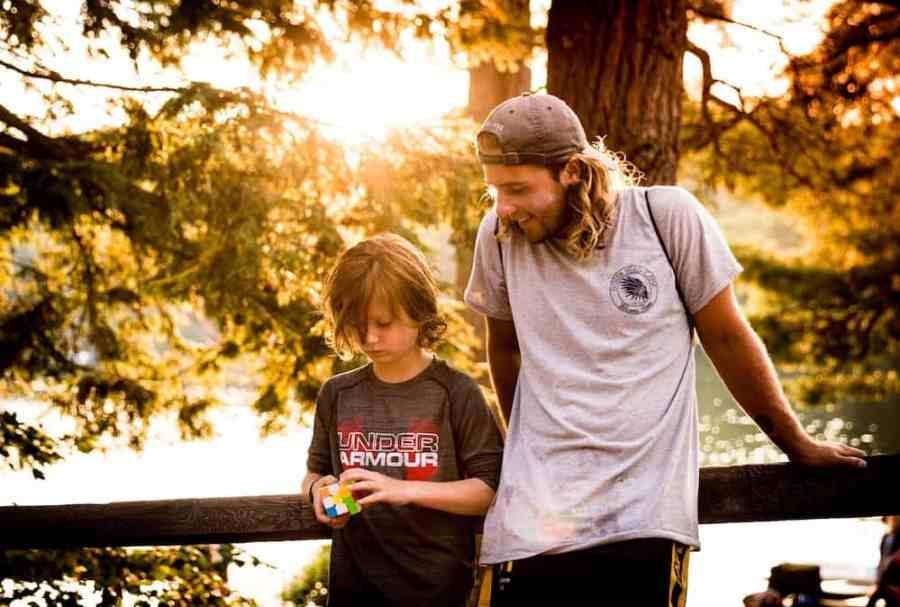 man standing beside boy playing rubik cube