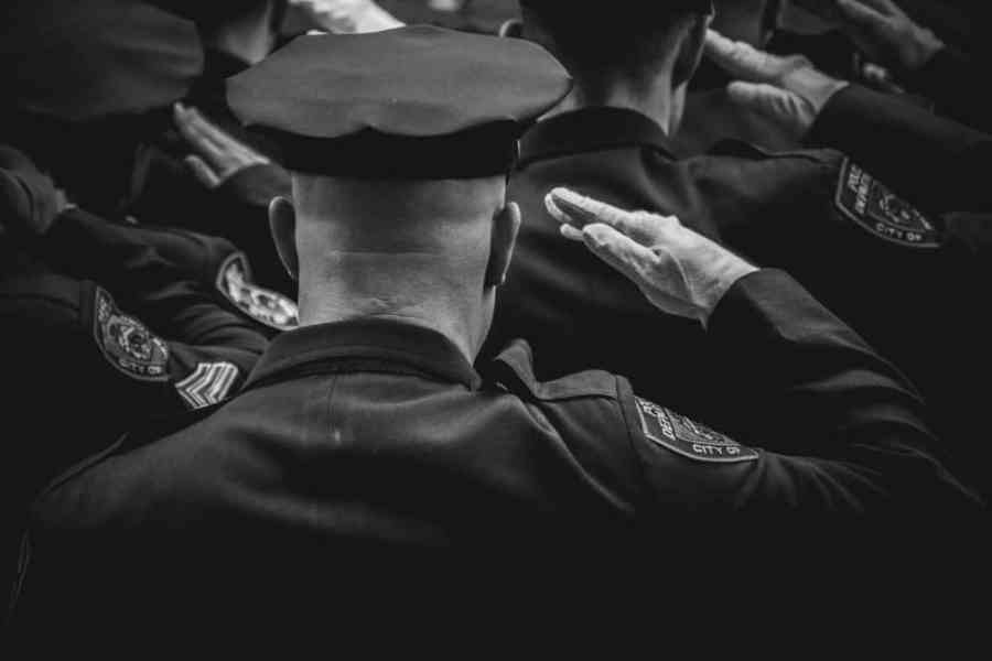 Black and White Photography of a Police Officer Giving Honor