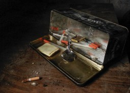 clear and red syringes inside open tin can near cigarette butt