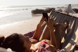 woman using mobile phone while relaxing in a hammock on the beach