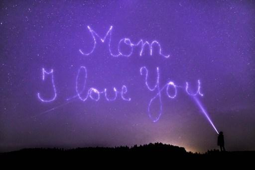 Ένα παιδί γράφει μαμά σε αγαπώ με ένα φακό