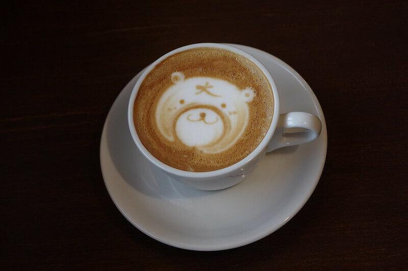 une tasse à café dans laquelle on voit un panda qui sourit