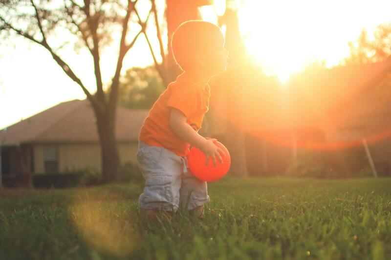 enfant qui joue au ballon au coucher de soleil