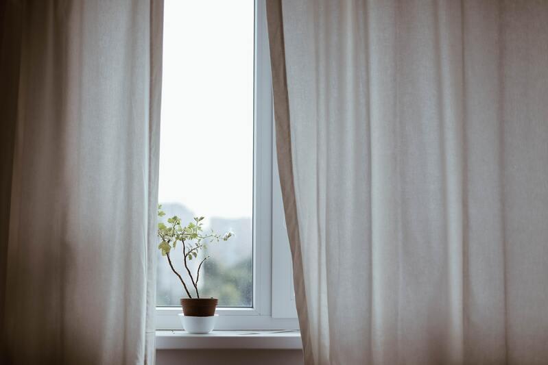 rideau blanc entrouvert avec plante en pot dans l'ouverture