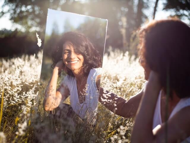 self-love-meditations-affirmations-woman-looking-mirror-smiling