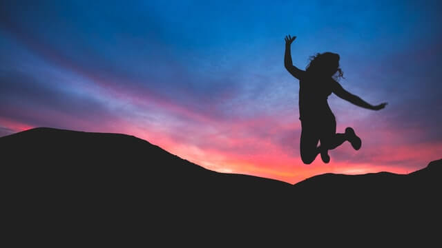 making-decision-defeat-procrastination-girl-happy-jumping-colorful-sunset