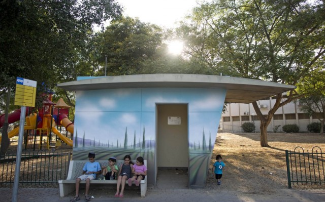 Israeli children sit next to a concrete protective shelter painted by Israeli artist Eliasaf Myara in the village of Kfar Maimon, located a few kilometers from the border with the Gaza Strip, Israel, 14 June 2015. The Israeli Defense Ministry has placed hundreds of small concrete protective shelters to all towns located near the Gaza Strip to protect its citizens from incoming rockets. On 08 July 2015, Israel will mark one year since the 2014 Israel–Gaza conflict, also known as Operation Protective Edge.