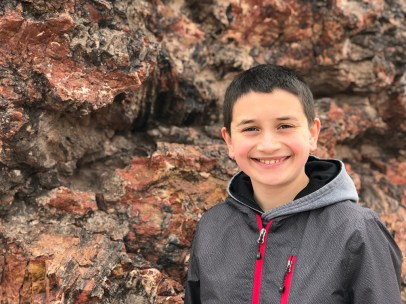 Carter Bourn STanding Next to a Petrified Tree Stump