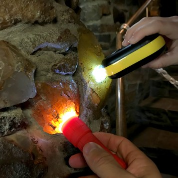 Kids Using Flashlights To Light Up The Agates In The Walls of Living Rock Studios