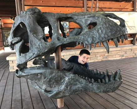 Carter Bourn Posing with a Giant Dinosaur Skull Fossil