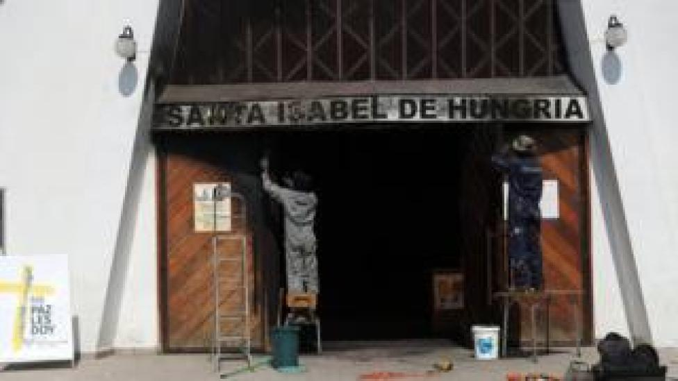 People repair the church of St. Elizabeth of Hungary, where a fire was set on 12 January