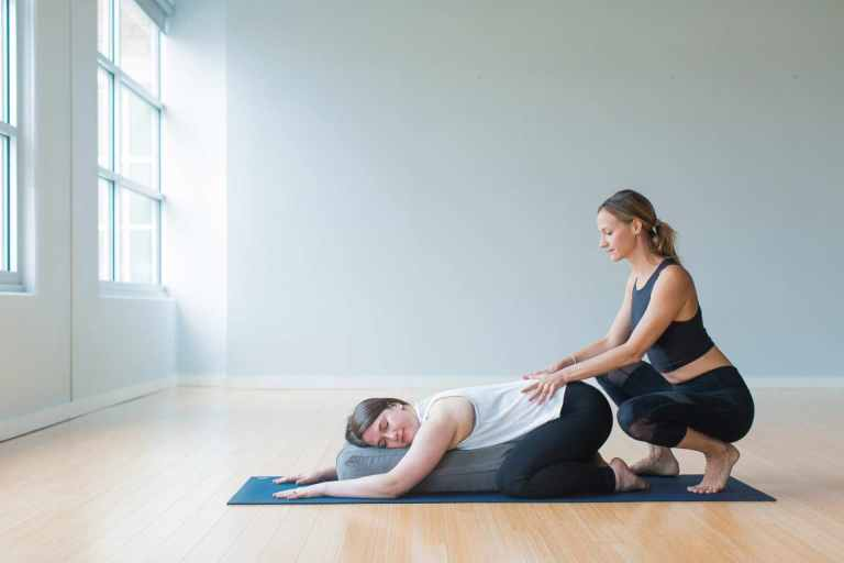 Yoga Teacher Training assisting a student during Yin yoga class style in laying down compression