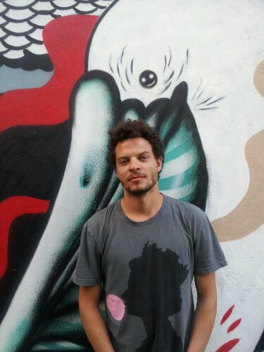 Mateus Bailon by one of his murals on Heneage Street