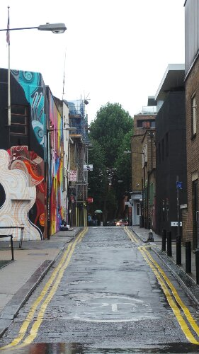 Looking up Chance Street from Bethnal Green Road.  Reka's Fallen Angel can be seen with the MadC piece beyond