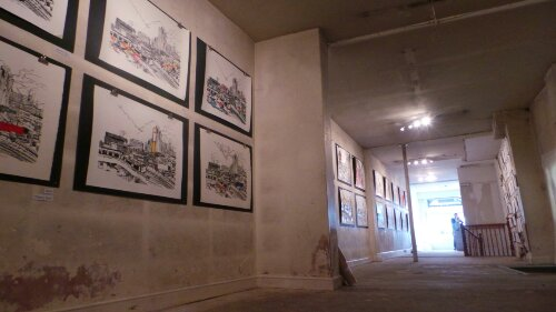 A long wall exhibits the collaborations with various artists