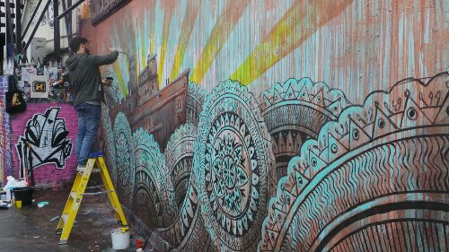 Beau uses a variety of brushes to compete the mural