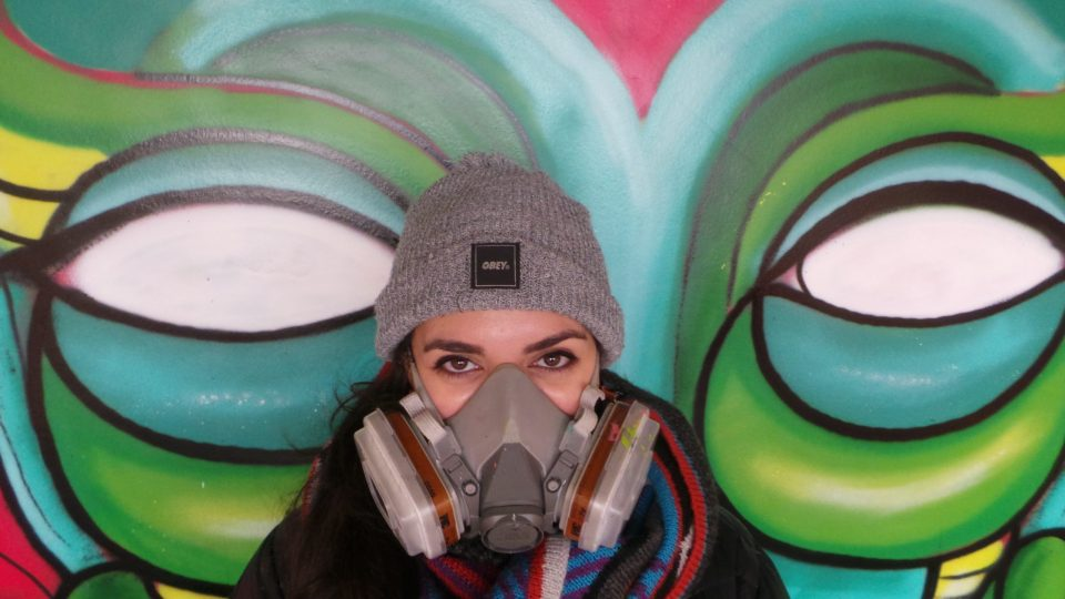 Amara poses by her mural with just the eyes to do