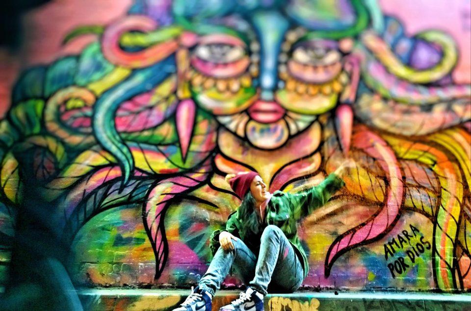 Amara Por Dios next to her typically dynamic mural