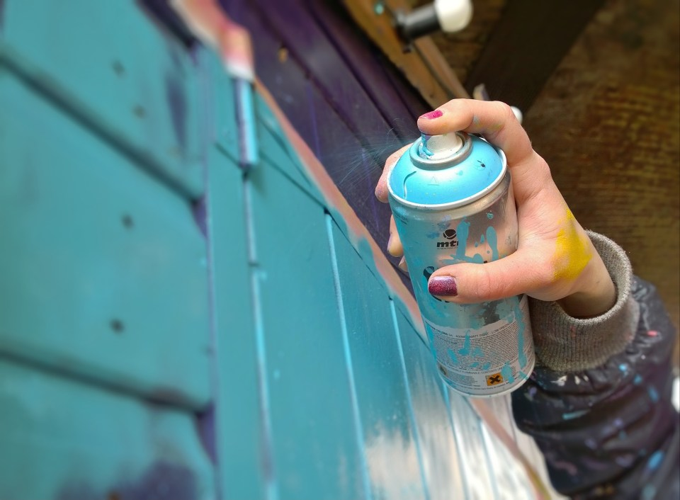 Zabou spraying her mural onto one of the sheds at Camden Market