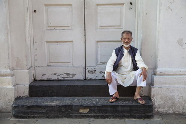 A man sits on the steps  of the Lane