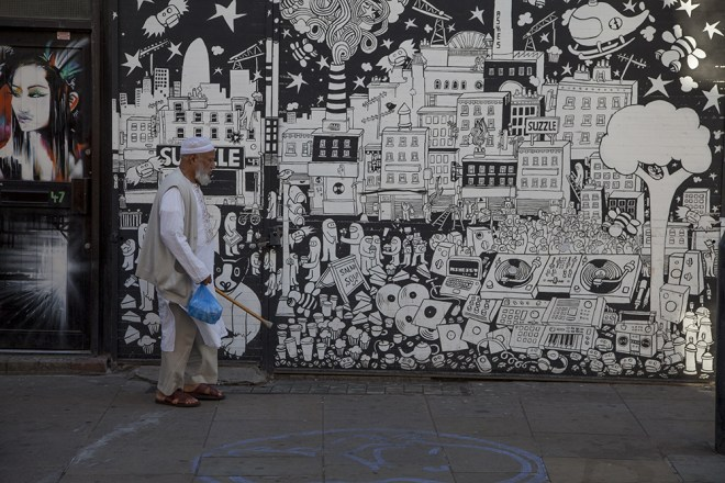 A man walks past work from Ashes57 and Dan Kitchener on the shutter of a cafe