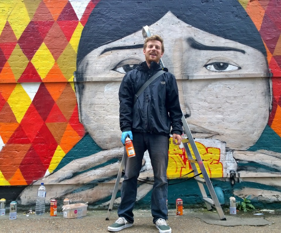 Ryan Kai next to his mural on Sclater Street