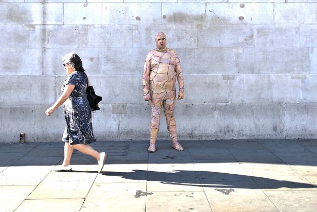 Lewis Burton dressed from head to toe in chicken skin standing in front of the National Gallery