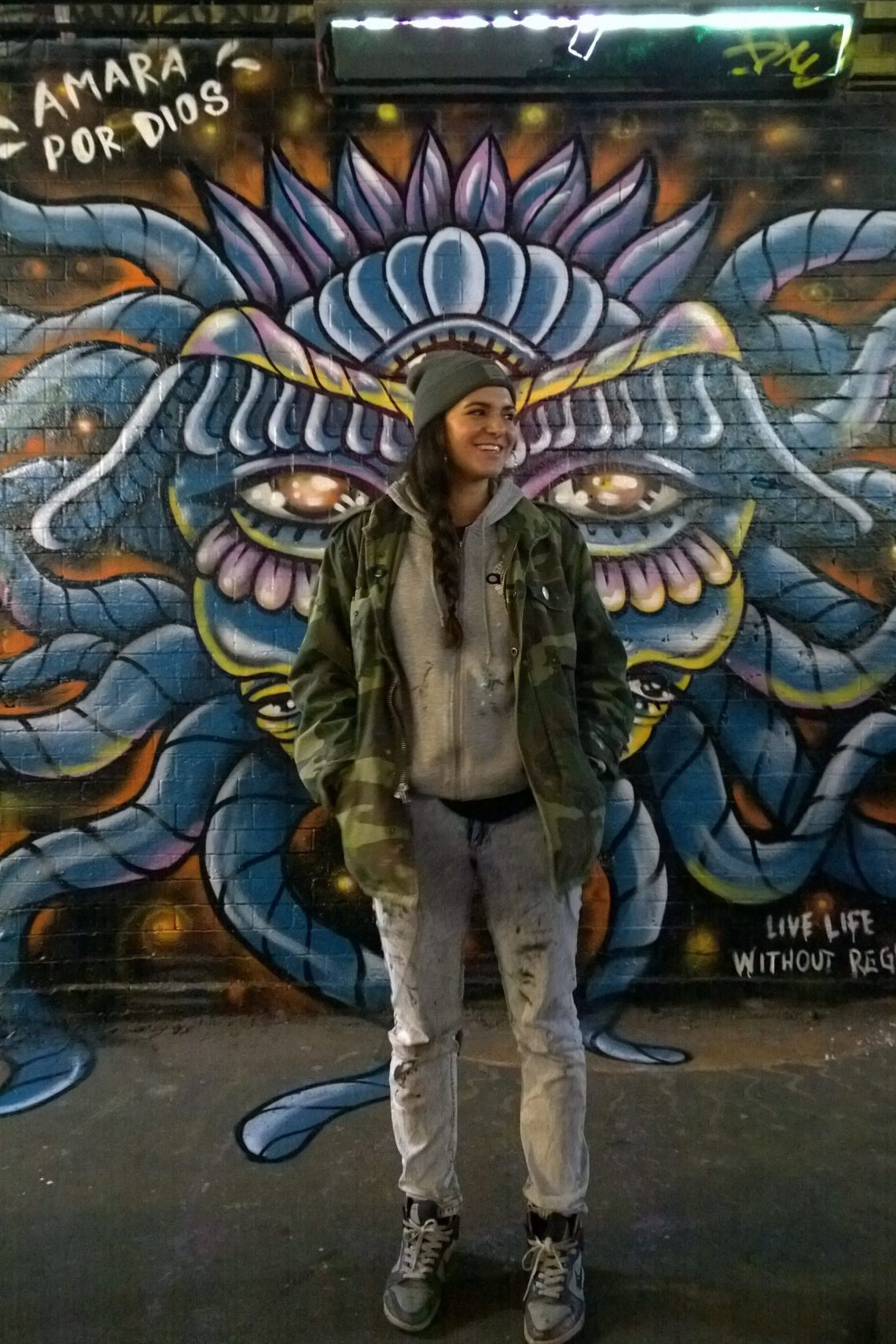 Amara Por Dios next to her tribute piece in the tunnel