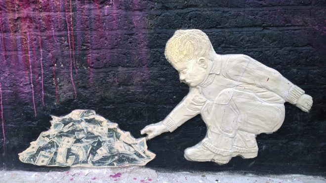 China Girl's child playing with a rubbish heap full of money