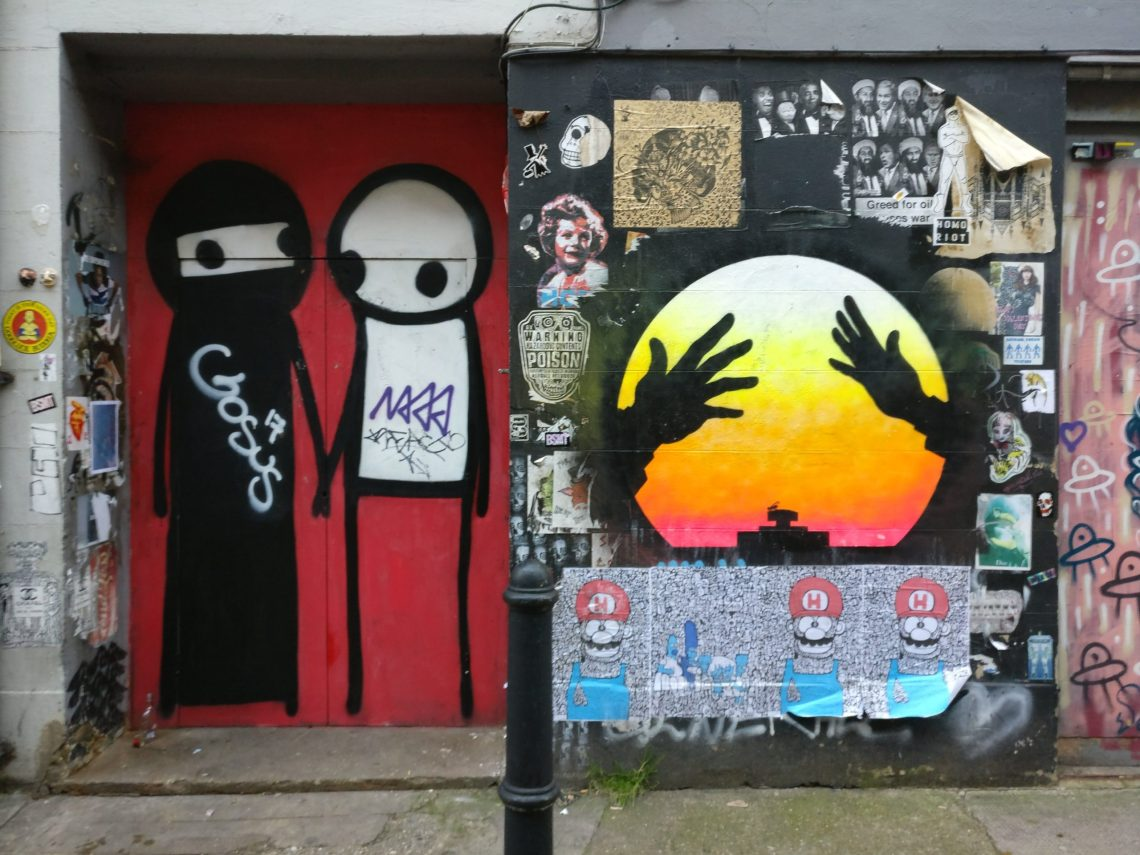 A Couple Holding Hands on the Street by Stik can be found on the Shoreditch Street Art Map