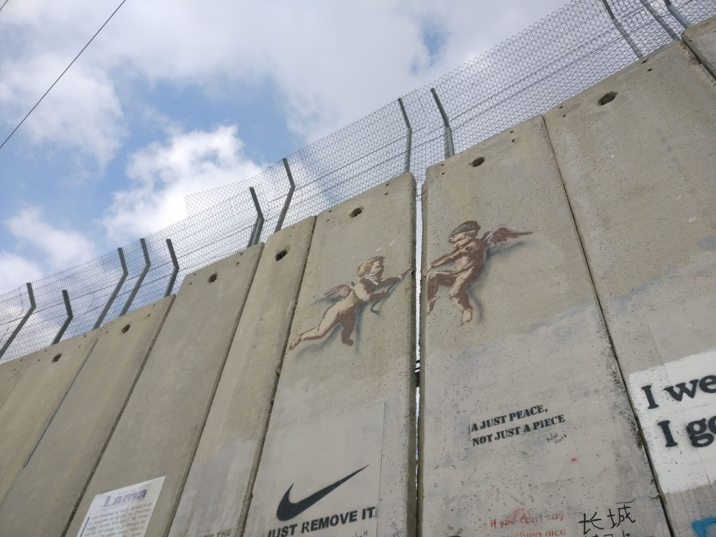 Cherub paintings by Banksy prise open the separation barrier in Bethlehem