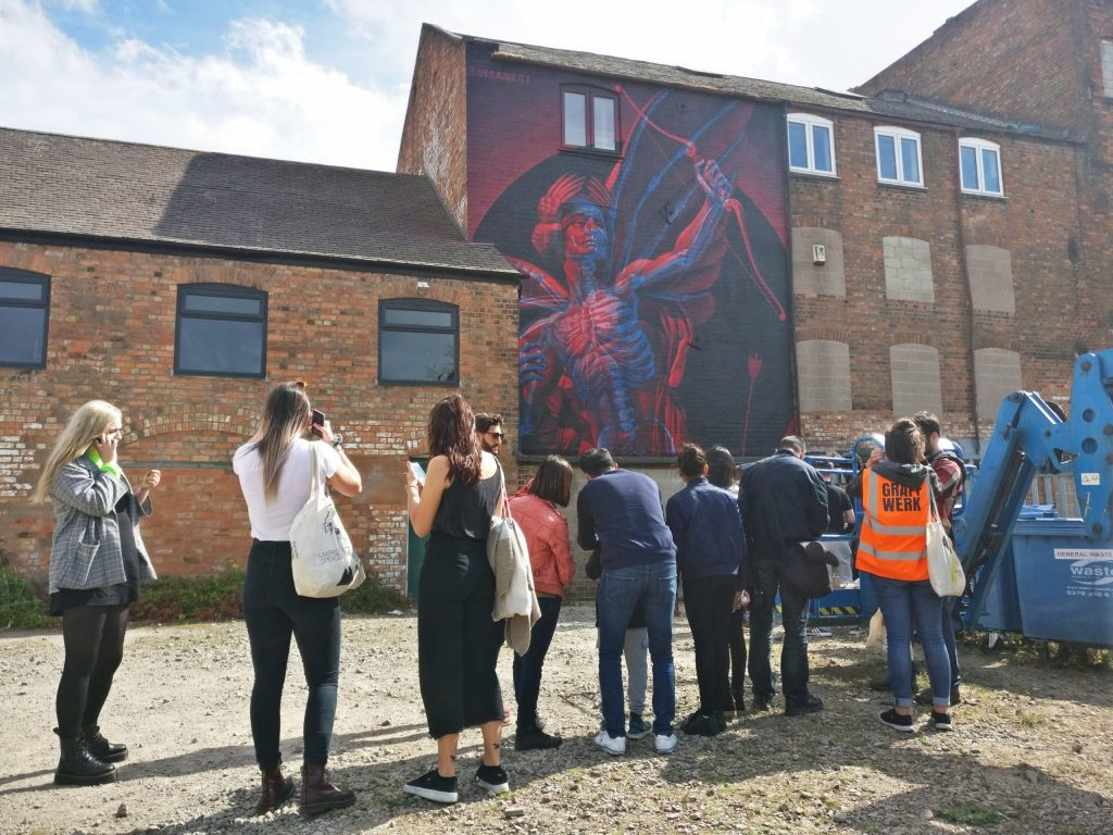 Visitors to Leicesters Bring the Paint Festival look at a mural by Insane51 at the Graffwerk HQ