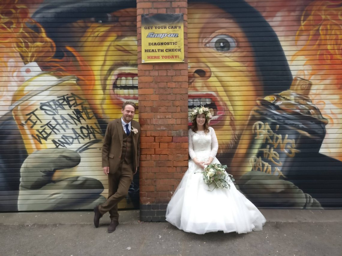 A newly married couple pose by street art from Tasso at the Leicester Bring the Paint festival