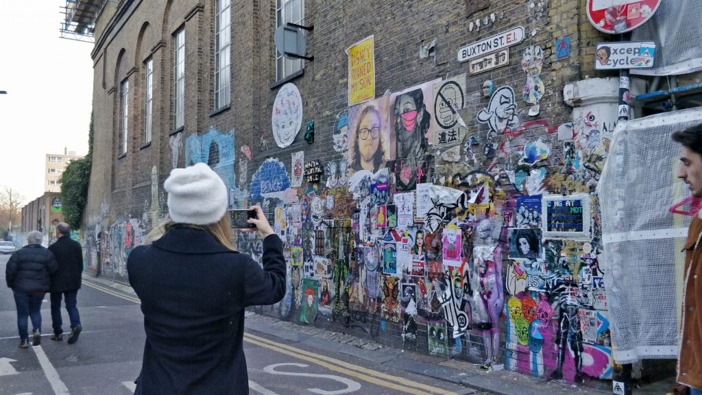 A tourist takes pictures of graffiti on Buxton Street near Brick Lane