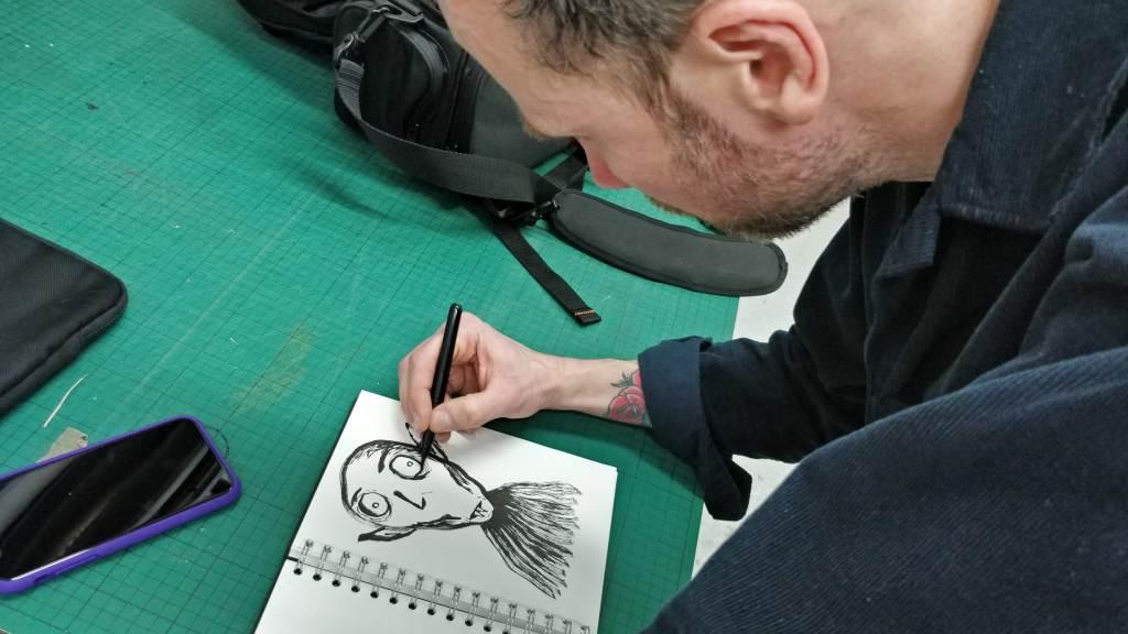 Eelus sketching in a black book
