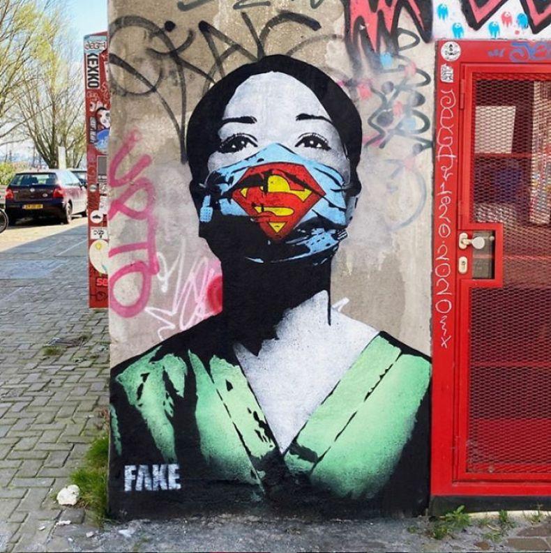 Coronavirus street art from Fake in Amsterdam. it shows a nurse wearing a superman mask