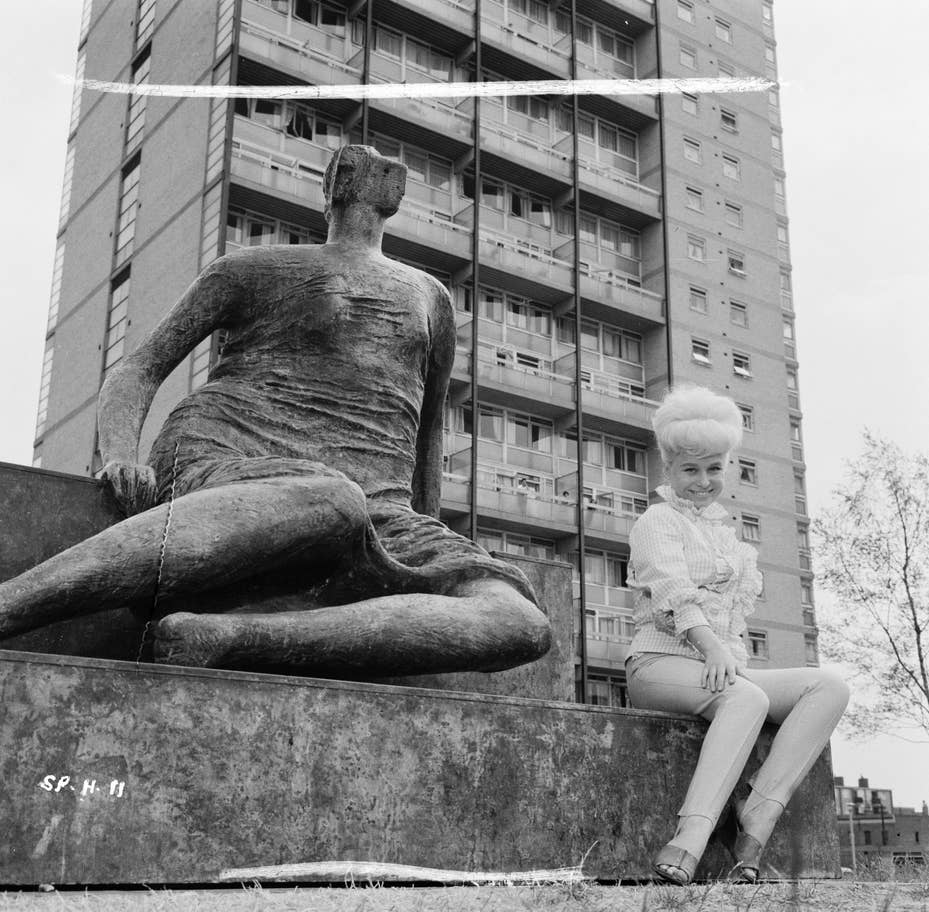 Barbara Windsor poses next to Henry Moores Draped Seated Woman statue in Stepney Green