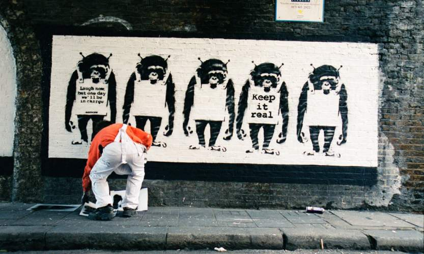 Banksy painting his five monkeys stencil on Rivington Street in 2000