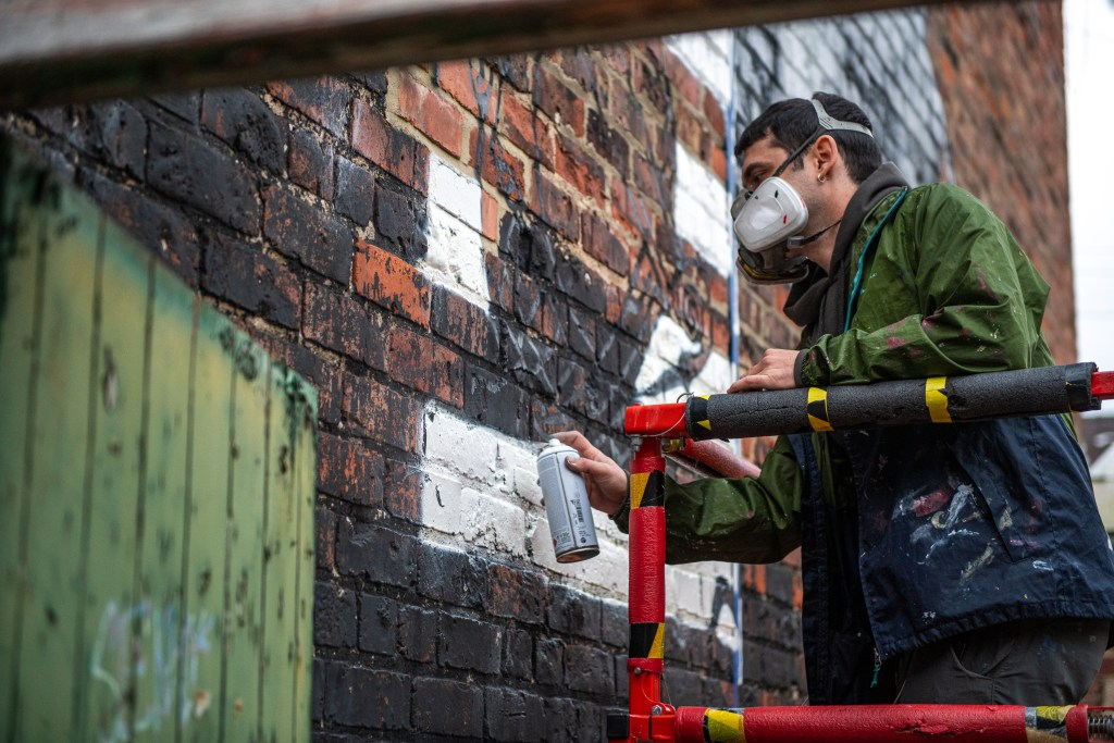 Spanish artist Jay Kaes working on the Arthur Wharton mural in Darlington