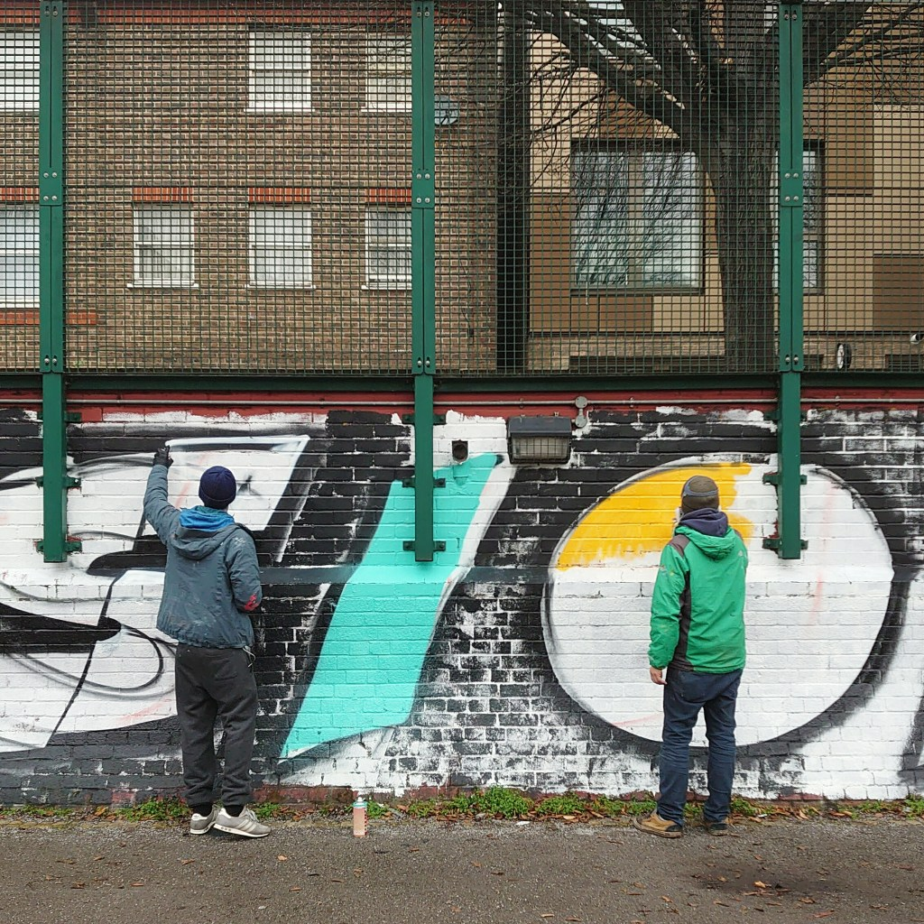 Graffiti writers Coma and SkyHigh painting their mural in Chicksand Street Park