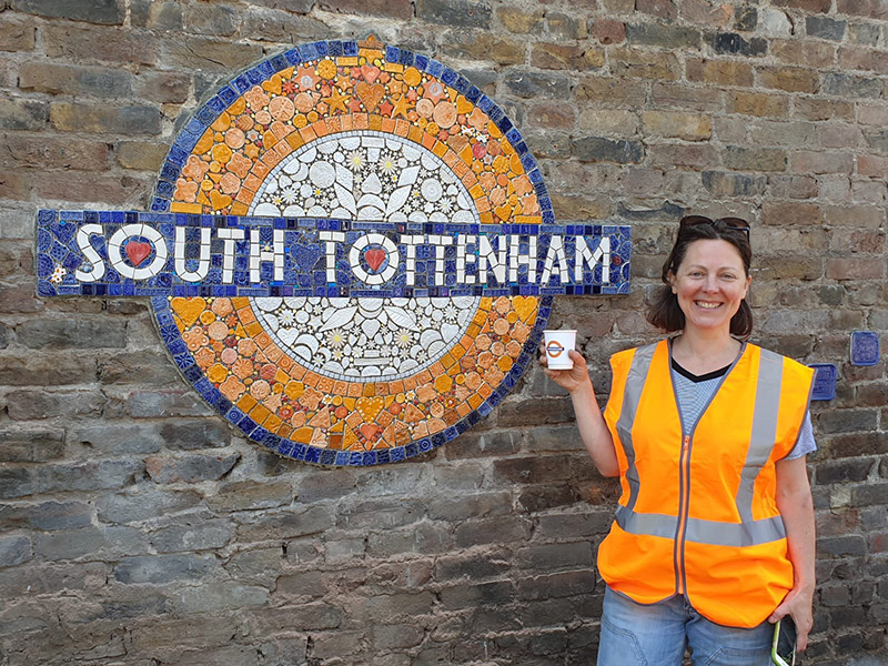 Maud Milton stands with a coffee next to the South Tottenham mosaic roundel