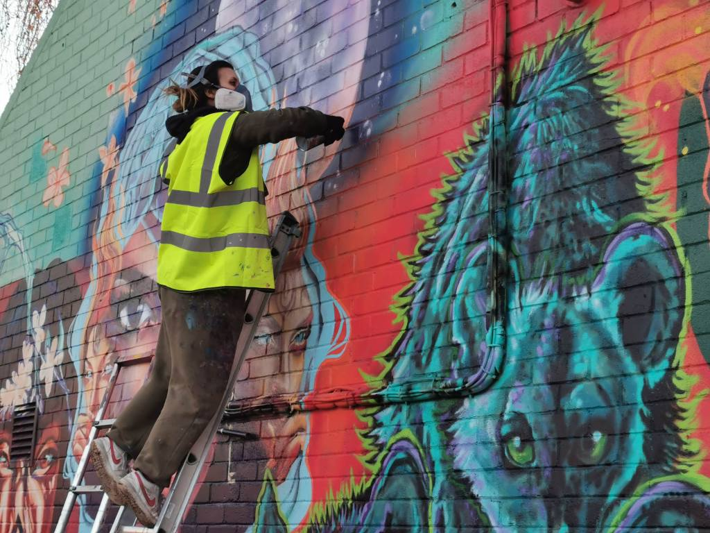 Van Jimmer painting with the WOM collective on their mural in Brixton