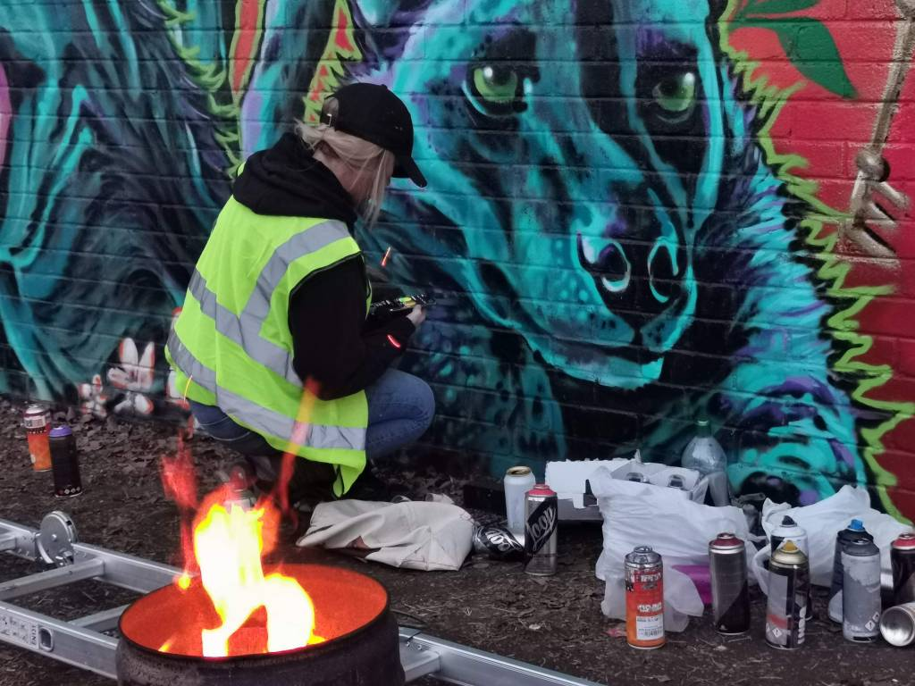 Layla Cope by a fire painting the wom collective wall in brixton