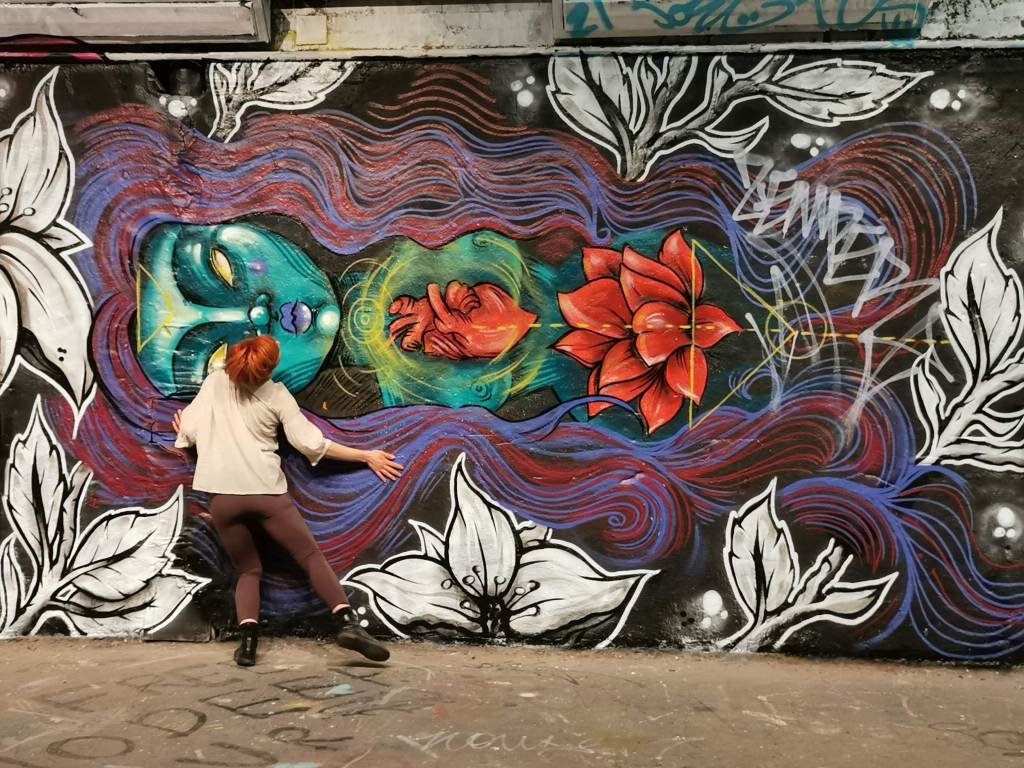 A performer dances against a mural, painted by Elno, in the Leake Street Tunnel