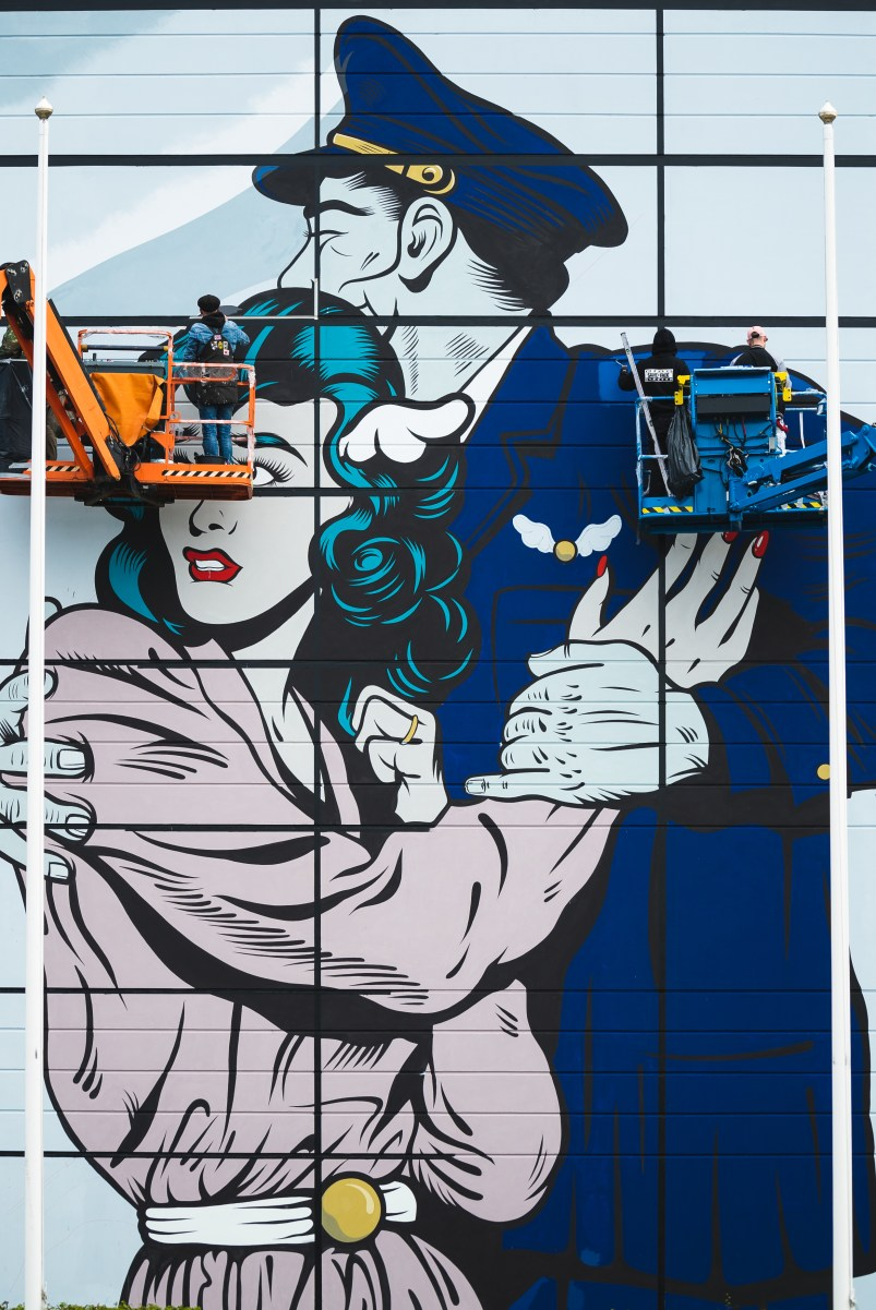 D*Face painting his mural at the airport in Gothenburg